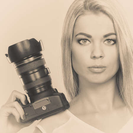 Photographer girl shooting images. Attractive blonde woman taking photos with camera. Filtered photo photo