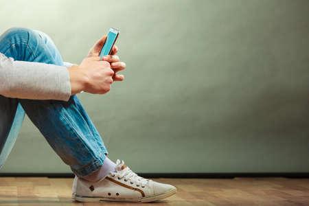 手携帯電話、コピー領域のグランジ背景のスマート フォンを使用して床の上に座って男を抱きかかえた 写真素材