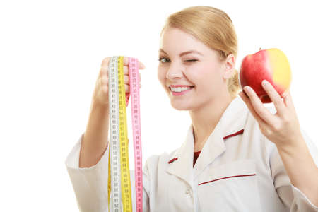 dietitian: Slim down dieting concept. woman in white lab coat recommending healthy food. Doctor specialist dietitian holding fruit apple and measure tape isolated.