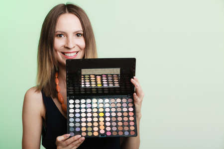 makeover: Cosmetic beauty procedures and makeover concept. Woman holds makeup professional palette. Make-up applying. Green background Stock Photo