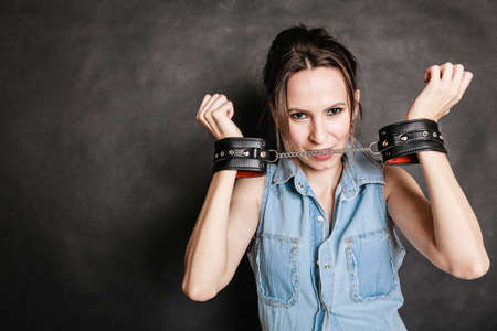 handcuffs girl: Arrest and jail. Criminal woman prisoner girl showing leather handcuffs on gray. Punishment.