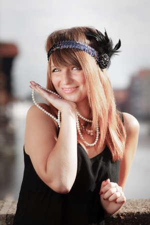 flapper: Retrato de la chica de la aleta. Mujer de la vendimia de la moda retro estilo de rugiente 1920 en diadema con collar de perlas, al aire libre. Fondo de la ciudad