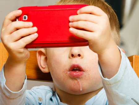drool: Technology generation. Happy childhood. Little boy child dirty mouth drooling, eating breakfast playing with mobile phone at table. Home. Stock Photo