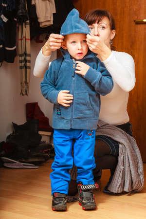 ni�os vistiendose: Mujer madre en el pasillo delante de ponerse la capa del ni�o Foto de archivo