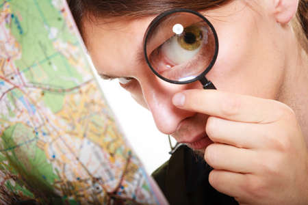 lupa: Travel vacation concept. man looking through a magnifying glass loupe at map
