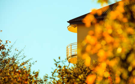 Villa in autumn, home with balcony in a suburb at fall on blue sky background Stock Photo