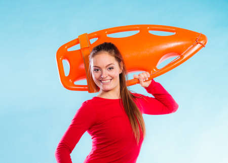 Accident prevention and water rescue. Young woman female smiling lifeguard on duty holding float lifesaver equipment on blue photo