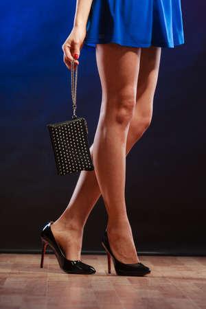 piernas con tacones: Celebraci�n concepto de discoteca y noche de la moda - mujer en vestido azul de la celebraci�n del bolso, bailando en el club, parte del cuerpo piernas femeninas en los zapatos de tac�n alto en el piso de las partes