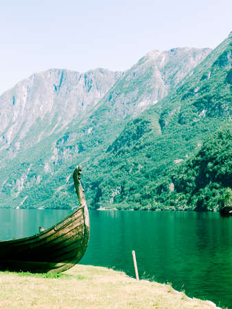 sognefjord: Tourism and travel. Mountains and fjord Sognefjord in Norway, Scandinavia. Old viking boat on seashore.