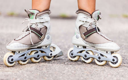 roller blade: Enjoying roller skating rollerblading on inline skates sport in park. Outdoor activities. Part of human legs in sport shoes.