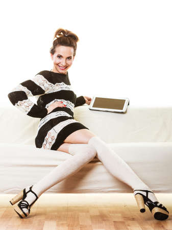 Technology internet concept. Fashion trendy woman sitting with tablet on white couch at home photo