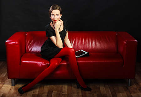 red couch: Technology internet business concept. Fashion woman retro style sitting with tablet on red couch Stock Photo