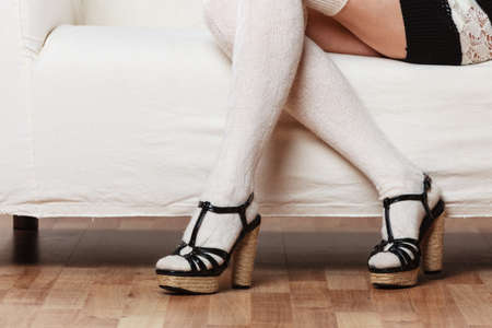 white stockings: Fashionable woman legs. Girl in woolen white stockings black heeled shoes relaxing on sofa