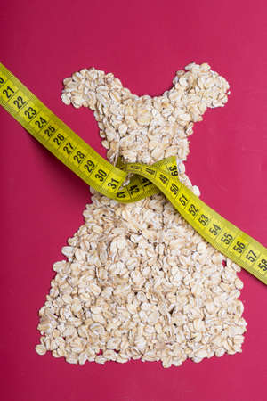 waist down: Dieting healthy eating slim down concept. Female dress shape made from oatmeal with measuring tape around thin waist on red
