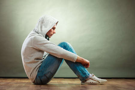 Young people and emotions concept. Sad hooded man teen boy with headphones sitting on floor grunge background Stock Photo