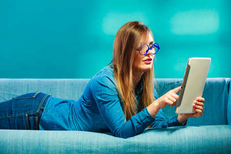 Modern technology education internet concept. Fashion student girl in glasses with tablet relaxing on blue color photo