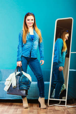 Fashion and shopping. Woman in full length wearing denim with bag. Attractive female shopper looking in mirror, standing in clothes store. Blue color photo