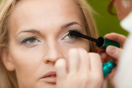 makeover: Cosmetic beauty procedures and makeover concept. Closeup part of woman face eye makeup detail. Make up artist applying mascara.