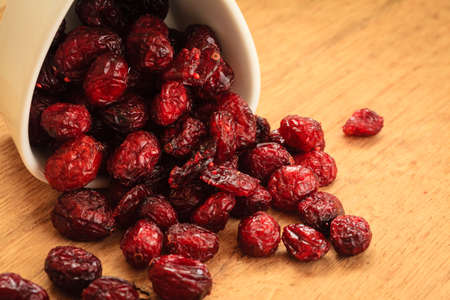 dehydrated: Healthy high fiber foods, organic nutrition. Close up dried cranberries cranberry fruit in bowl on wooden table. Stock Photo