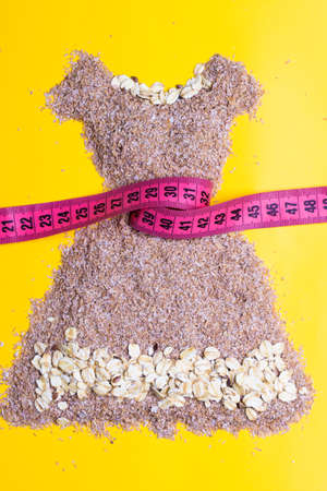 Dieting healthy eating slim down concept. Female dress shape made from cereal bran with measuring tape around thin waistline on yellow