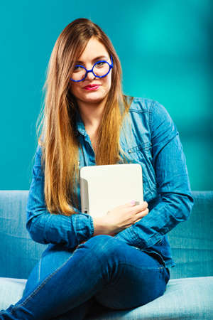 Modern technology education internet concept. Fashion woman student girl in glasses wearing denim with tablet sitting on couch blue color photo