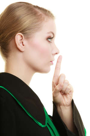 legality: Law court or justice concept. Womn lawyer attorney classic polish black green gown finger on lips. Confidential information.