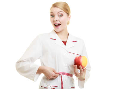 dietitian: Slim down dieting concept. woman in white lab coat recommending healthy food. Doctor specialist dietitian holding fruit apple measuring her waist isolated. Stock Photo