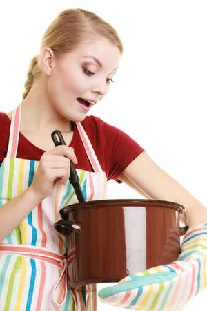 Happy housewife or chef in colorful kitchen apron with pot of soup and ladle isolated studio shot photo