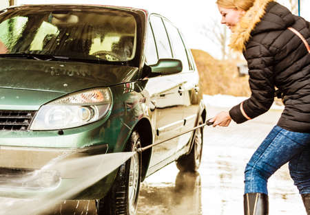 pressured: Manual auto wash. Young attractive blonde woman washing the dirty car with foam and pressured water at service station on open air