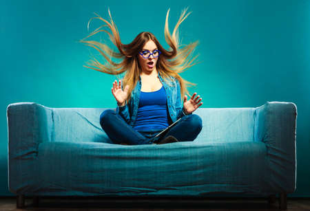 Technology internet concept. Fashion woman wearing denim sitting with tablet on couch hair blowing face expression blue color Stock Photo