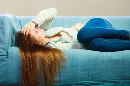 enfermo: Concepto emoción negativa Soledad. Joven mujer estresada triste acostado en el sofá en casa Foto de archivo