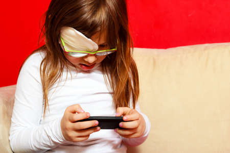 Technology generation. Little girl child in glasses with medicine plaster playing games on smartphone mobile phone at home photo