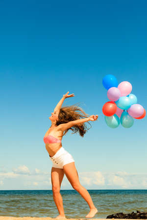 Summer holidays, celebration and lifestyle concept - attractive athletic woman teen girl jumping with colorful balloons outside on beach, sunny day photo