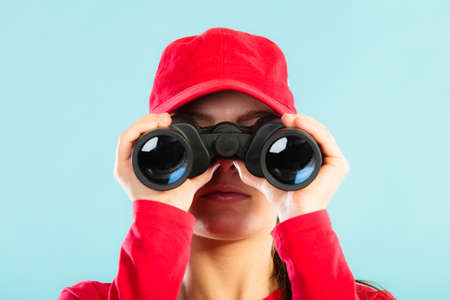 observant: Accident prevention and water rescue. Closeup girl in red lifeguard outfit on duty looking through binocular on blue