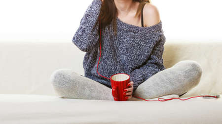 red couch: People leisure relax concept. Woman casual style red big headphones listening music mp3, sitting on couch at home relaxing drinking hot tea coffee