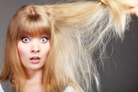 dry hair: Haircare. Blonde woman with her damaged dry hair shocked face expression gray background