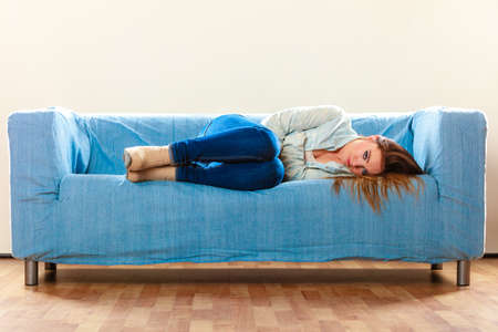 negative emotion: Loneliness negative emotion concept. Young sad stressed woman lying on couch at home