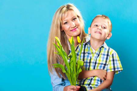 lad: Boy celebrating mothers day. little child lad giving flowers yellow tulips to his mom mother studio shot on blue Stock Photo