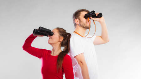 security search: Young man and woman lifeguards on duty or tourist couple looking through binocular studio shot on gray Stock Photo