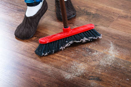 foots: Cleanup housework concept. Closeup broom and female foots. Cleaning woman sweeping wooden floor. Stock Photo