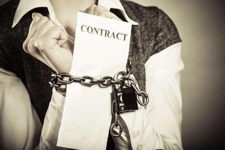 Business concept. D'affaires sérieux avec des mains enchaînées tenant contrat