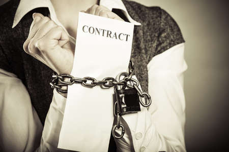 Business concept. Serious businesswoman with chained hands holding contract Foto de archivo