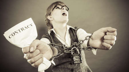 roped: Business and stress concept. Furious businesswoman in glasses with chained hands holding contract grunge background Stock Photo