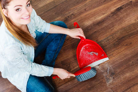 brooming: Cleanup housework concept. cleaning woman sweeping wooden floor with red small whisk broom and dustpan unusual high angle view