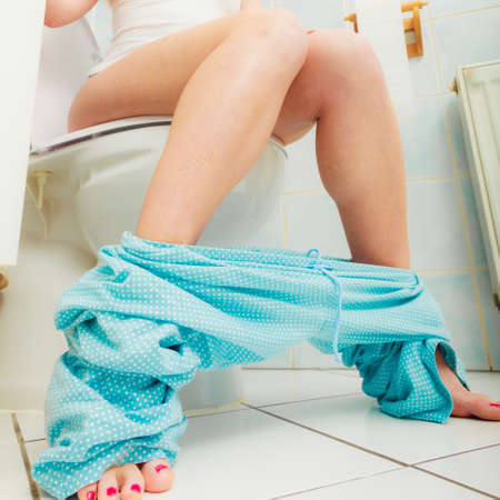 a toilet stool: Woman with constipation or diarrhoea sitting on toilet with her blue pajamas down around her legs