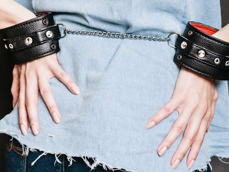 manacles: Arrest and jail. Closeup leather handcuffs on female hands, criminal woman prisoner girl back view on dark. Punishment.