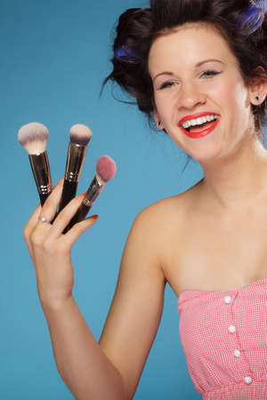 Cosmetic beauty procedures and makeover concept. Woman in hair rollers holding makeup brushes set on blue photo
