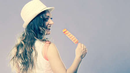 woman fashionable: Summer vacation happiness concept. Smiling joyful and cheerful woman fashionable female model eating popsicle ice pop cross filter