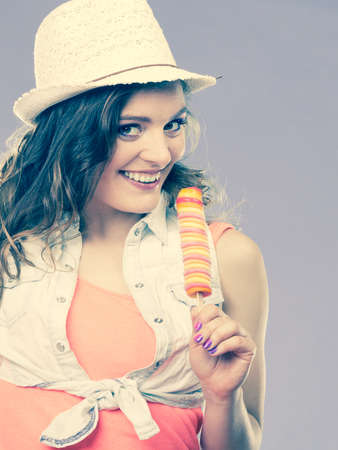woman fashionable: Summer vacation happiness concept. Smiling joyful and cheerful woman fashionable female model eating ice pop cross filter