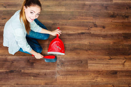 cleanup: Cleanup housework concept. cleaning woman sweeping wooden floor with red small whisk broom and dustpan unusual high angle view